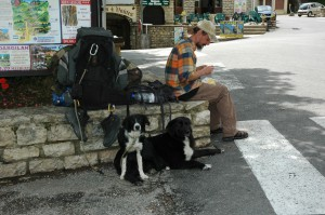 A man and his dogs pause to rest from their trek in a tiny stone walled village in Lozere.