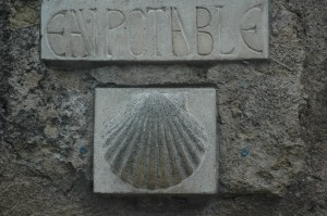 A scallop shell, which often is worn by those walking the Way of St. James, also marks the trail itself and hostels hosting walkers.