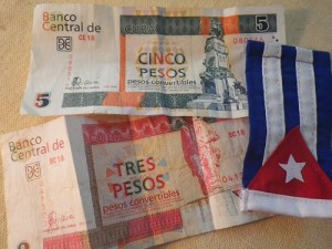Five  CUC and  three CUC convertible peso notes are shown with a souvenir Cuban flag. The CUC currency, designed to be exchanged for other currencies brought to Cuba by visitors, isn't used by Cubans