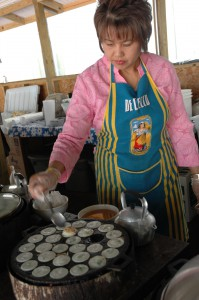 A Thai women tends to dumplings she's cooking for those coming to the Sunday morning food sale at her Temple.